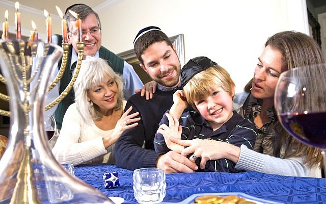 No need to be a Scrooge on Hanukkah... (Family Hannukah Scene image via Shutterstock)