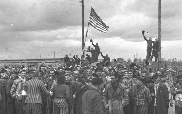 Dachau, Germany. Concentration camp prisoners raise the American flag after liberation. (Courtesy Yad Vashem Archives)