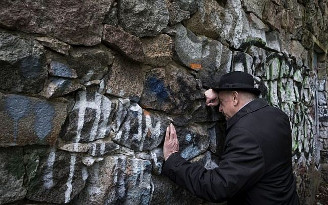 Shmuel Levin, chairperson of the Jewish religious community of Vilnius and Lithuania, leans against a wall of the power substation built of tombstones from a Jewish cemetery in Vilnius, Lithuania, May 13, 2015 (AP/Mindaugas Kulbis)