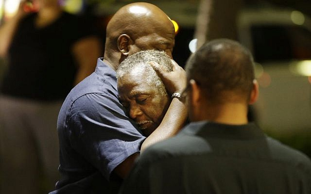 Worshippers embrace following a group prayer across the street from the scene of a shooting on June 17, 2015, in Charleston, South Carolina. (David Goldman/AP)