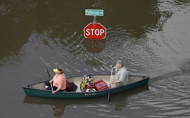 In this aerial photo, people canoe through floodwaters past a stop sign near Bear Creek Park Saturday, May 30, 2015, in Houston. (AP/David J. Phillip)