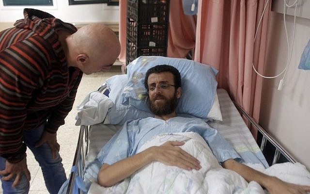 Mohammed al-Qiq, a Palestinian prisoner who carried out hunger strike, talks to a man in a hospital in the northern Israeli town of Afula on February 5, 2016. (Ahmad Gharabli/AFP)