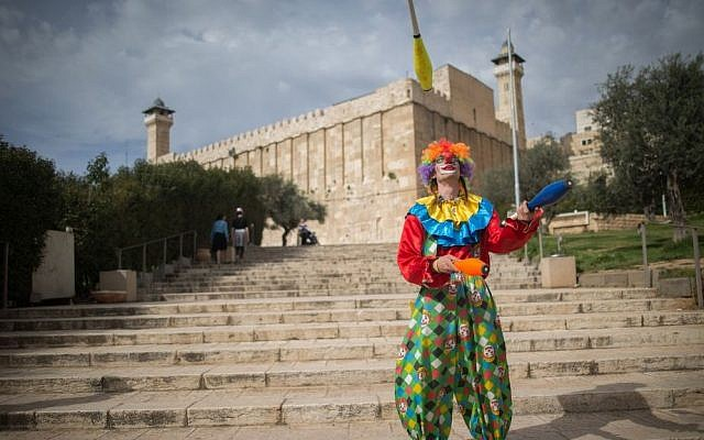 A man in a clown costume juggles during the annual parade marking the Jewish holiday of Purim in the West Bank town of Hebron on March 24, 2016. (Yonatan Sindel/Flash90)