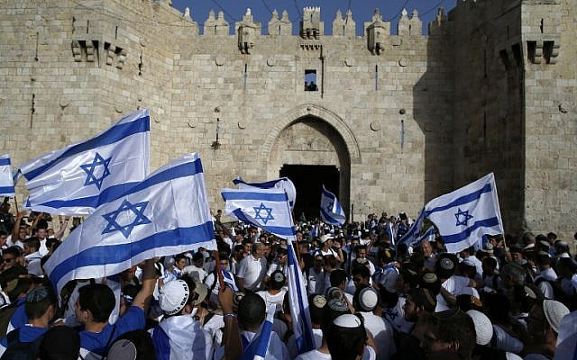Israelis wave national flags as they take part in an annual march marking Israel's 1967 capture and subsequent annexation of the eastern half of Jerusalem, outside Damascus Gate in Jerusalem's Old City on June 5, 2016. (AFP PHOTO / AHMAD GHARABLI)