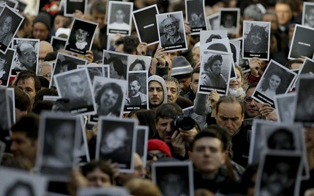 People hold up pictures of those who died in the AMIA Jewish center bombing that killed 85 people as they commemorate the attack's 22nd anniversary in Buenos Aires, Argentina, July 18, 2016. (AP Photo/Natacha Pisarenko/File)