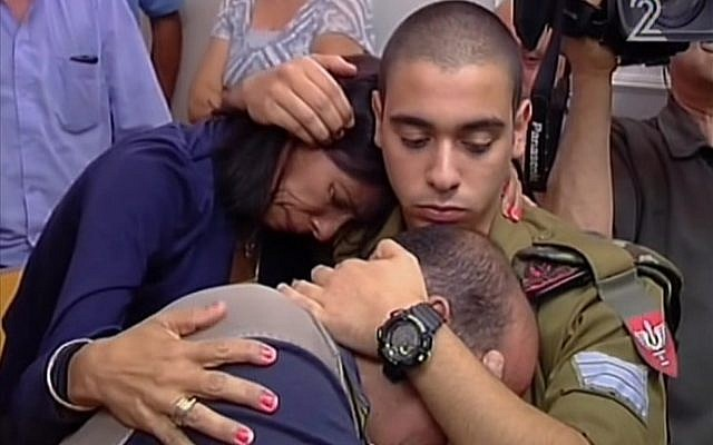 Elor Azaria hugging his mother and father in Jaffa military court on July 5, 2016. (screen capture: Channel 2)