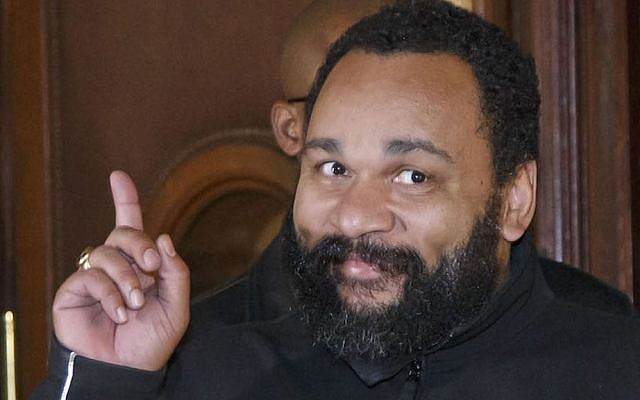 French comedian Dieudonne M'Bala M'Bala gestures to the media as he leaves a Paris court house, Wednesday, Feb. 4, 2015.  (AP Photo/Michel Euler)