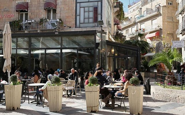Illustrative: Israelis enjoy the sun as they sit outside at Cafe Rimon in downtown Jerusalem on January 14, 2013. (Nati Shohat/Flash90)