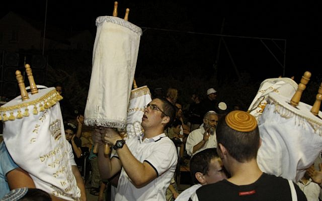 """Israelis dance with the Scroll of a Torah during the Jewish holiday of Rejoicing of the Torah inGush Etzion at the West Bank, 30 September 2010 . Simchat Torah which means """"rejoicing with/of the Torah"""" is one of the happiest days in the Jewish calendar and is marked with festivities in synagogue that include singing, dancing and (typically) a moderate consumption of alcohol.Photo by Gershon Elinson / Flash90"""