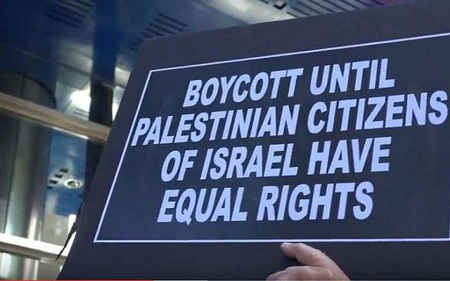 Illustrative: A protester against anti-BDS legislation holds a sign in front of Governor Cuomo's NYC offices on June 9, 2016. (screen capture: YouTube)