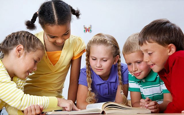 Portrait of pupils looking at page of encyclopaedia at reading lesson