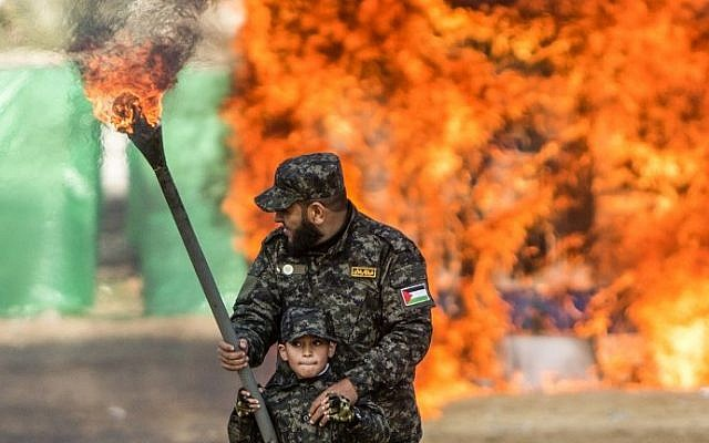 A Palestinian man helps a boy set fire to an Israeli flag during a graduation ceremony for Hamas security forces in Gaza City on January 22, 2017. (AFP PHOTO / MAHMUD HAMS)