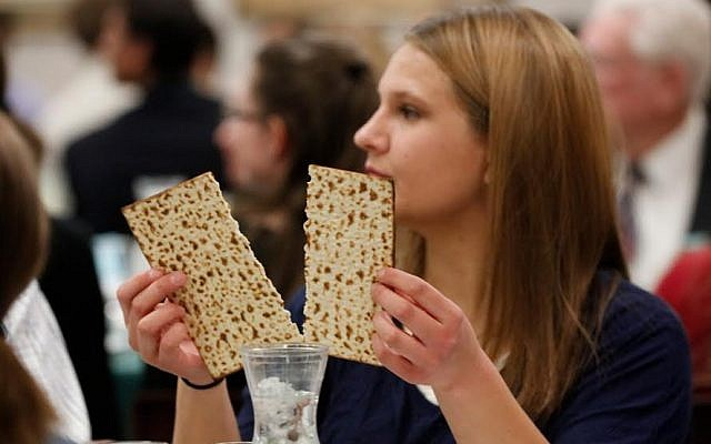 Illustrative: A woman breaks the middle matzah at a model seder on March 11, 2016. (Jaren Wilkey/BYU)