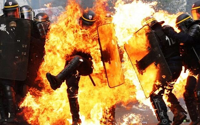 French CRS anti-riot police officers are engulfed in flames as they face protesters during a march for the annual May Day workers' rally in Paris on May 1, 2017. (AFP PHOTO / Zakaria ABDELKAFI)