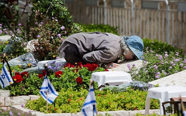 A woman kisses the grave of a fallen soldier on the eve of Memorial Day at the Kiryat Shaul military cemetery in Tel Aviv, Sunday, April 30, 2017. (AP Photo/Ariel Schalit)