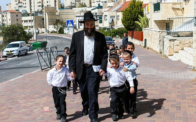 Illustrative: An ultra-Orthodox teacher takes the kids from his class to a walk in the sun on March 12, 2013, in the West Bank settlement of Beitar Ilit. (Nati Shohat/Flash90/File)