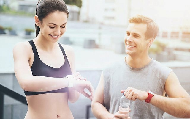 Couple checking fitness trackers. (iStock)