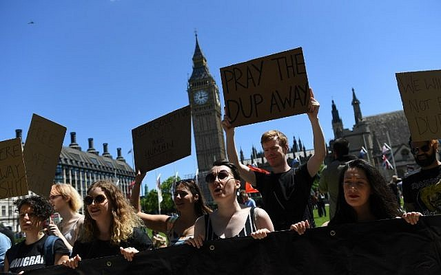 """Illustrative: Protesters hold up a banner that reads """"London-Irish Abortion rights Campaign"""" as they protest in Parliament Square in front of the Houses of Parliament in central London against the Democratic Unionist Party (DUP), June 10, 2017. (AFP Photos/Justin Tallis)"""