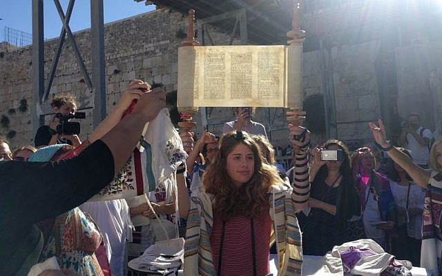 Illustrative: A young member of Women of the Wall holds up the miniature Torah scroll during the monthly Rosh Hodesh service on June 25, 2017, in the women's section of the Western Wall plaza, just before Netanyahu froze the Kotel Agreement. (Melanie Lidman/Times of Israel)