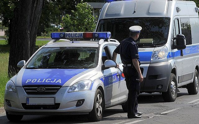 Illustrative photo of a Polish police officer, accompanied by two service vehicles, performing spot checks on passing traffic. (GFDL Cezary p/Wikipedia)
