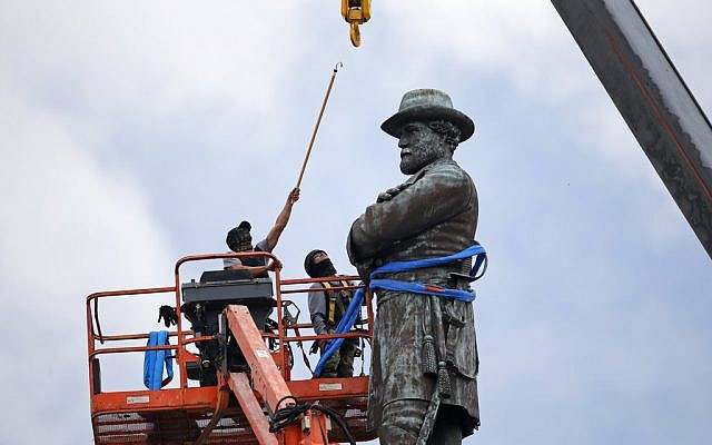 In this Friday, May 19, 2017, file photo, workers prepare to take down the statue of former Confederate Gen. Robert E. Lee, which stands over 100 feet tall, in Lee Circle in New Orleans. (AP Photo/Gerald Herbert, File)