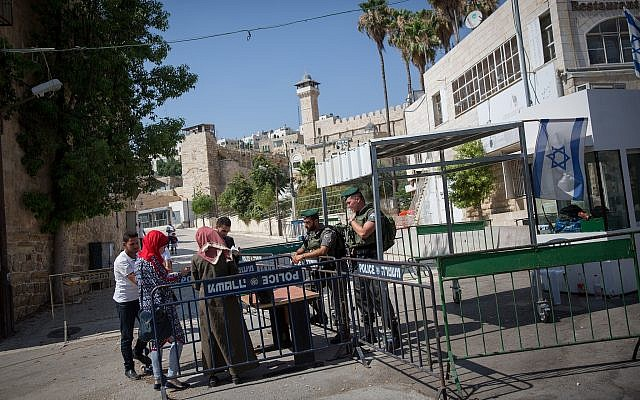 Border Police officers check the ID of Palestinian women at the entrance to the Tomb of the Patriarchs in the West Bank city of Hebron on July 9, 2017. (Miriam Alster/Flash90)
