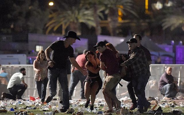 People carry a person at the Route 91 Harvest country music festival after a gunman opened fire on crowds attending the event, in Las Vegas, Nevada, October 1, 2017. (David Becker/Getty Images/AFP)