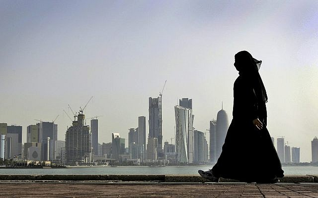 In this file photo from May 14, 2010, a Qatari woman walks in front of the city skyline in Doha, Qatar. (AP Photo/Kamran Jebreili, File)