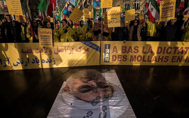 "Protesters hold placards reading ""Support Iranians risen up against the religious dictatorship"" as they stand behind a portrait of Iranian President Hassan Rouhani with shoe marks over it during a demonstration in support of the Iranian people amid a wave of protests spreading throughout Iran, on January 3, 2018, in Paris.(AFP PHOTO / Lionel BONAVENTURE)"