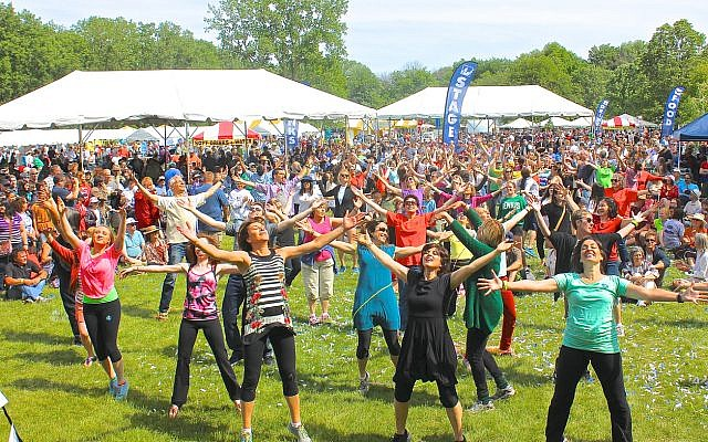 "At the Greater Chicago Jewish Festival, ""flash mob"" dancers perform an Israeli folk dance medley as part of the biennial outdoor event, which included music stages, art and craft fair, kosher food, children's activities and was attended by over 20,000 people during the day, in Morton Grove, IL, on June 8, 2014. (iStock)"