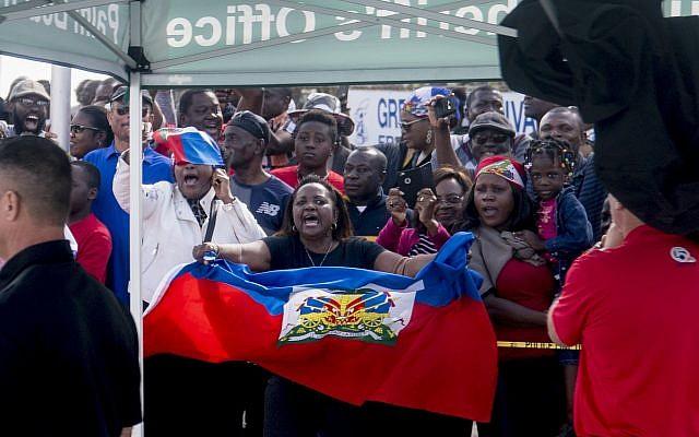 Haitians line the sidewalks as President Donald Trump's motorcade returns to Mar-a-Lago in West Palm Beach, Florida, on January 15, 2018. (AP Photo/Andrew Harnik)