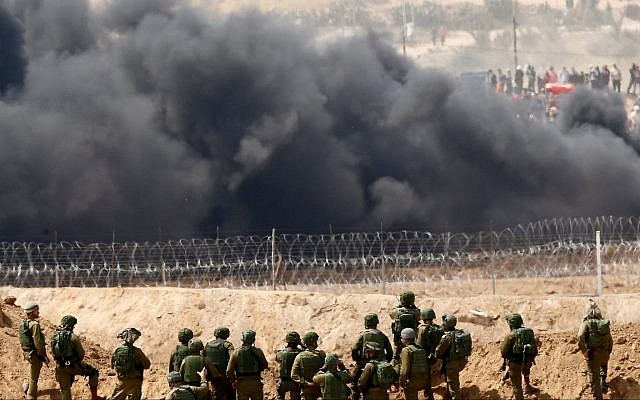 Illustrative: Black smoke rises from tires burned by Gaza protesters at the border with Israel, with Israeli soldiers seen in the foreground, April 13, 2018. (AP Photo/Ariel Schalit)