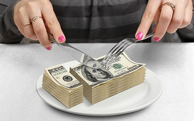 US taxes, dollars, hands cut money on plate, reduce funds concept. (via iStock)