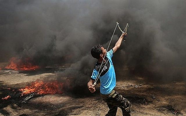A Palestinian man uses a slingshot during clashes with Israeli forces along the border with the Gaza strip east of Khan Younis on May 14, 2018 (AFP PHOTO / SAID KHATIB)