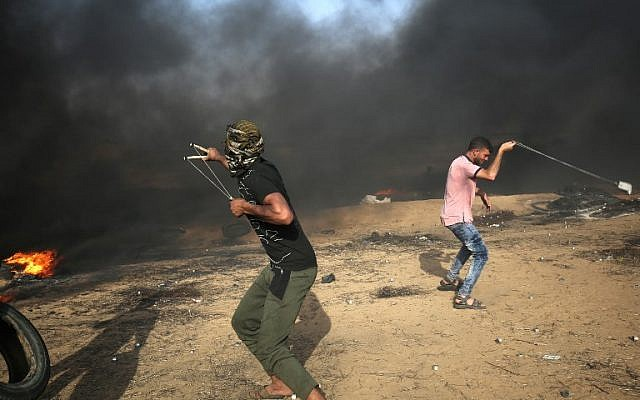 Palestinian demonstrators use slingshots to hurl rocks at Israeli forces during clashes along the border with the Gaza Strip east of Khan Younis on May 18, 2018. (AFP Photo/Said Khatib)