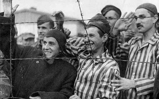 Survivors in Dachau greet their American liberators. Source: USHMM