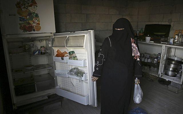 Samia Hassan shows her family's nearly empty refrigerator in Gaza City, May 31, 2018. (AP Photo/Adel Hana)