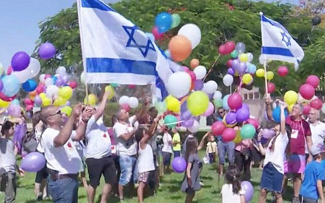 Children and residents of Kibbutz Nir Am release balloons carrying candy towards the Gaza Strip on June 15, 2018. (Screen capture: Hadashot TV News)