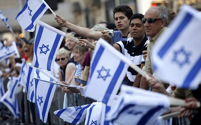 People wave Israeli flags while watching the Salute to Israel Parade in New York, May 31, 2009. (AP Photo/Seth Wenig)