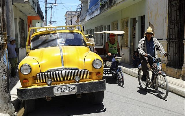 Men riding bicitaxis pass a 1950s auto of unknown origin on a Camagüey side street. (Larry Luxner)