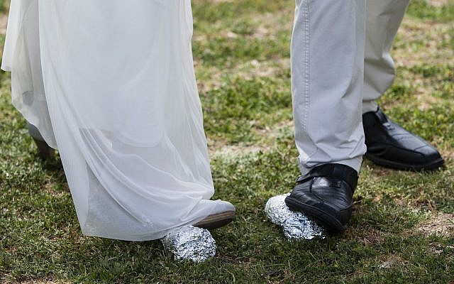 The legs of a bride and groom are seen as they break two glasses concluding their Reform Jewish wedding ceremony held in front of the Knesset, Israel's parliament in Jerusalem, on March 18, 2013, in protest of the Orthodox Rabbinate's monopoly on marriage licensing and the lack of civil marriages in Israel. (Flash 90)