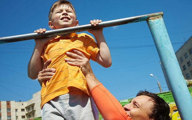 Illustrative. Kid doing chin-ups in the park. (iStock)