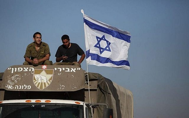 Israeli soldiers seen on top of a truck at their termporary set up military camp near the Israeli border with Gaza on July 24, 2014. (Yaakov Naumi/Flash90)