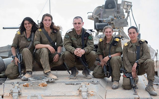 Head of the IDF Armored Corps Brig. Gen. Guy Hasson, center, poses on a tank with the army's first female tank commanders, June 28, 2018. (Israel Defense Forces)
