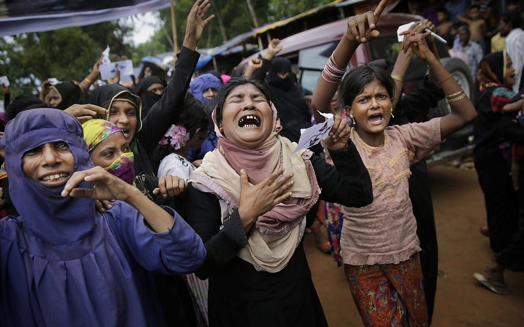 Rohingya women cry and shout slogans during a protest rally to commemorate the first anniversary of Myanmar army's crackdown on Rohingya Muslims, Kutupalong refugee camp in Bangladesh, Saturday, Aug. 25, 2018. (AP Photo/Altaf Qadri)