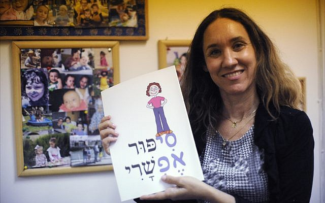 Shira Zagury, CEO of the Cystic Fibrosis Foundation of Israel, holds up a children's book about the disease at her Ramat Gan office. (Larry Luxner)
