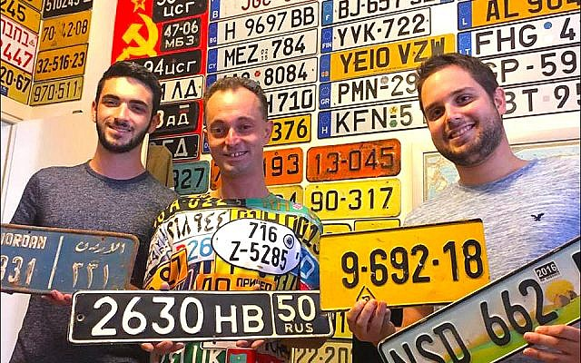 Israeli license plate collectors, displaying their favorite examples from Jordan, Russia, Israel and Swaziland, gather at the Ness Ziona home of Yoav Katz, far right, to talk shop. (Larry Luxner)