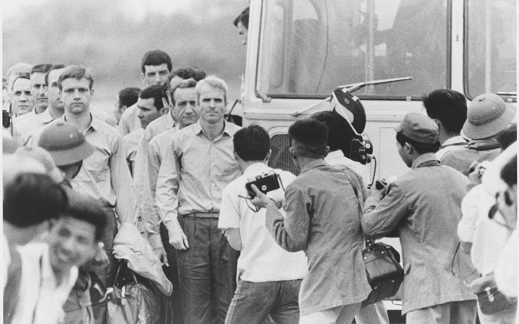 John McCain waiting for the rest of the group to leave the bus at airport after being released as a POW, 1973. (US Navy / PD via Wikipedia)