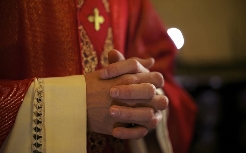 Catholic priest on altar praying with hands joined during mass service in church (iStock)