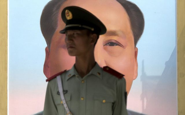 A Chinese paramilitary policeman stands watch against the portrait of the late Chinese leader Mao Zedong on Tiananmen Gate in Beijing, Friday, Sept. 1, 2017. (AP Photo/Andy Wong)